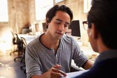 2 дизайнера обсуждают документ во время встречи в офисе Стоковое Фото