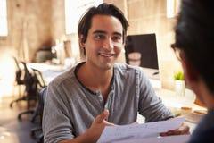 2 дизайнера обсуждают документ во время встречи в офисе Стоковое Изображение