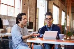 2 дизайнера сидят на таблице встречи работая на таблетке цифров Стоковые Фотографии RF