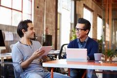 2 дизайнера сидят на таблице встречи работая на таблетке цифров Стоковая Фотография