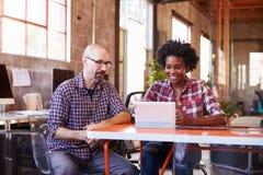 2 дизайнера сидят на таблице встречи работая на таблетке цифров Стоковые Изображения