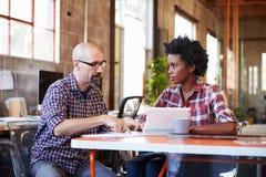 2 дизайнера сидят на таблице встречи работая на таблетке цифров Стоковые Фото