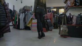 Избалованная привлекательная девушка подростка держа хозяйственные сумки и идя в пятки в магазине одежды от центра мола - видеоматериал