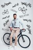 Избежание движения Во всю длину хорошего смотрящ человека с бородой полагаясь на его велосипеде против серой предпосылки с рукой стоковая фотография rf