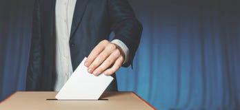 Избиратель человека кладя голосование в голосуя коробку Концепция свободы демократии около голубой стены стоковая фотография rf
