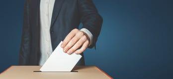 Избиратель человека кладя голосование в голосуя коробку Концепция свободы демократии на голубой предпосылке стоковые фото