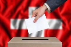 Избрание в Швейцарии - голосующ на урне для избирательных бюллетеней стоковые фотографии rf