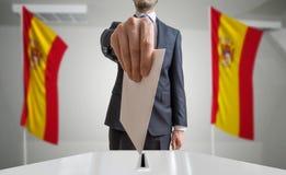 Избрание или референдум в Испании Избиратель держит конверт в голосовании руки вышеуказанном Флаги испанского языка в предпосылке стоковые фото