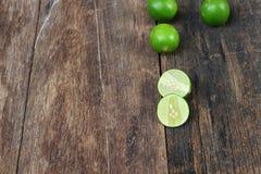 Известка зеленых лимона свежая и куска на деревянном столе Стоковое Фото