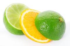 2 известки и отрезанного апельсина изолированными на белом пути клиппирования Стоковое Изображение