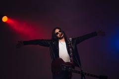 Известная мужская певица стоя на этапе с гитарой и микрофоном Стоковые Изображения RF