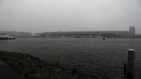 Известные здания центра города Амстердама на туманном дне Общий взгляд ландшафта обваловки города с шлюпками спешкы Промежуток вр сток-видео