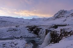 Известный водопад между замороженными скалистыми берегами mountai снега стоковые изображения