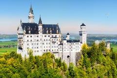 Известный замок Нойшванштайна, дворец сказки на изрезанном холме над деревней Hohenschwangau около Fussen Стоковые Изображения RF