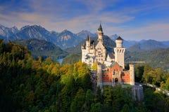 Известный замок Нойшванштайна сказки в Баварии, Германии, поздно вечером с голубым небом с белыми облаками стоковое изображение