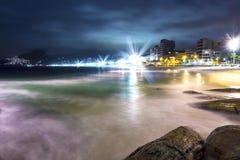 Известный пляж Ipanema вечером с красивыми светами и медленными волнами воды над утесами стоковые фотографии rf