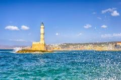 Известный старый маяк Chania в Крите с волнами моря брызгает тормозить на утесах со старым городом на предпосылке стоковые фотографии rf