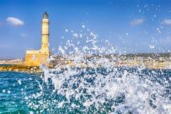 Известный старый маяк Chania в Крите с волнами моря брызгает тормозить на утесах со старым городом на предпосылке стоковое фото rf