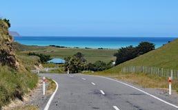 Извилистая дорога водит вниз к морю в Новой Зеландии стоковая фотография rf
