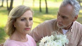 Извиняясь человек давая цветки женщине, кризису в отношениях, ссоре пар стоковое изображение