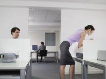 Извращенец наблюдая женского коллеги в офисе Стоковая Фотография