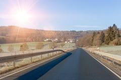 Изгибать дорогу между полями и деревьями в Германии Langgöns в зиме стоковые изображения