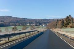 Изгибать дорогу между полями и деревьями в Германии Langgöns в зиме стоковые изображения rf