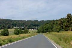 Изгибать дорогу между полями и деревьями в Германии Langgöns в Sommer стоковое фото