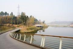 Изгибать ограженный footbridge на береге реки в солнечной зиме стоковое изображение rf