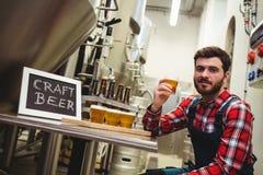 изготовитель держа стекло пива в винзаводе Стоковые Изображения RF