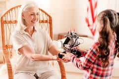 Излучающая старшая дама усмехаясь пока принимающ робототехническую машину от внучки стоковая фотография