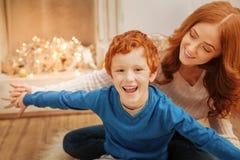 Излучающий ребенк усмехаясь в ободрении пока играющ дома Стоковая Фотография RF