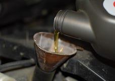 Изменение масла в двигателе автомобиля Заполнять масло через воронку Станция обслуживания автомобиля стоковые фото