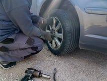 Изменение спущенной шины автомобиля заменить на аварийной ситуации п стоковое изображение