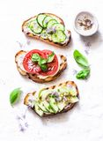 Изменения лета сандвичей - с плавленым сыром, авокадоом, томатом и огурцом на светлой предпосылке, взгляд сверху Здоровое питание Стоковое Изображение