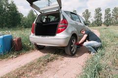 Изменения человека спущенная шина на его автомобиле стоковые изображения