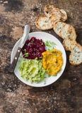 Изменения hummus Тыква, турмерин, авокадо, hummus бураков с оливковым маслом, семена сезама и микро- зеленые цвета на деревянном  Стоковое Изображение RF