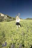 Измененное цифров, сверхконтрастное изображение белокурой девушки идя через зеленые поля заполнило с цветками lupine весной в Oja Стоковые Изображения RF