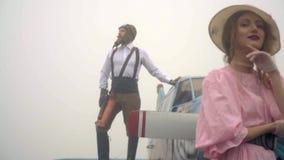 Измените направление с зверским пилотом который стоит на крыле самолета в тумане на женщине в розовом платье и белой шляпе видеоматериал