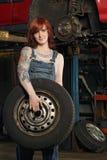 изменяя женские автошины механика Стоковая Фотография RF