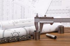 Измерение части металла с крумциркулем на предпосылке технических чертежей Стоковое Фото