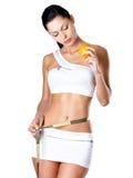 Измерения девушки вычисляют с измеряя лентой и апельсин держать Стоковые Фотографии RF
