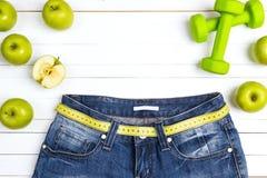 Измерьте ленту с джинсами голубой женщины, зелеными яблоками и dumbbels o Стоковое Изображение RF