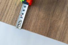 Измерять деревянный стол с зеленой и оранжевой покрашенной рулеткой стоковое изображение rf