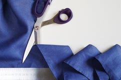 Измеряющ и режущ ткань Ножницы и фиолетовая linen ткань Стоковые Фотографии RF