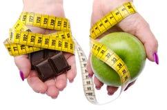 Измеряя лента вокруг рук женщины держа яблоко и chocola Стоковое Изображение RF