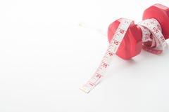 Измеряя лента обернутая вокруг красной гантели изолированной на белизне Стоковое Изображение RF