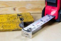 Измеряя инструменты в мастерской плотничества Стальная измеряя лента дальше Стоковое Фото