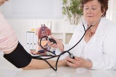Измеряя кровяное давление с аппаратурой прибора на докторе 2 w стоковые фото