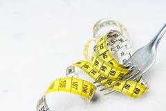 Измеряя лента желтый цвет, обернутый вокруг вилки лежа на w Стоковое Изображение